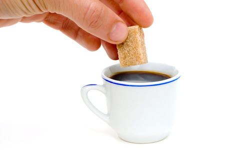 fine cane: a hand putting a sugar in a cup of coffee Stock Photo