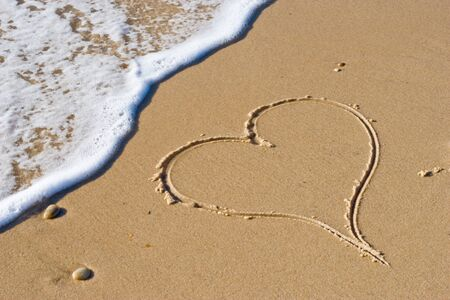 handwritten hearth on sand with wave approaching Stock Photo