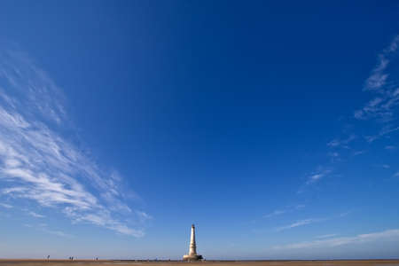 alone Cordouan lighthouse against large blue sky  photo