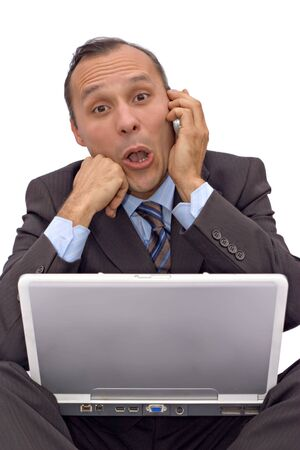 businessman with computer receiving bad news on mobile phone  photo