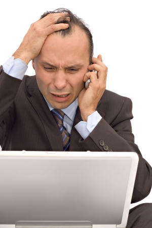 calamity: businessman receiving bad news on phone while checking on computer