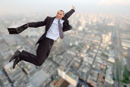 smiling businessman flying over a big city Stock Photo