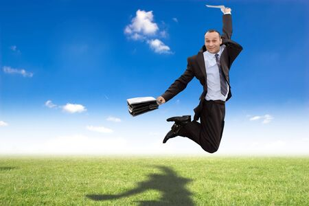 happy businessman jumping in green meadow with shadow on grass under blue sky Stock Photo