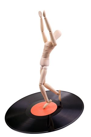 vintage concept: wood mannequin dancing on vinyl disc photo