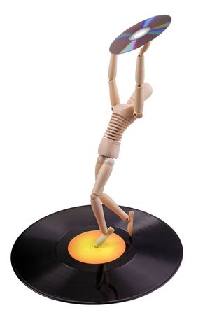 technology concept: wooden mannequin on vinyl disc holding compact disc photo