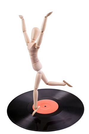 wooden mannequin dancing on old vinyl disc photo