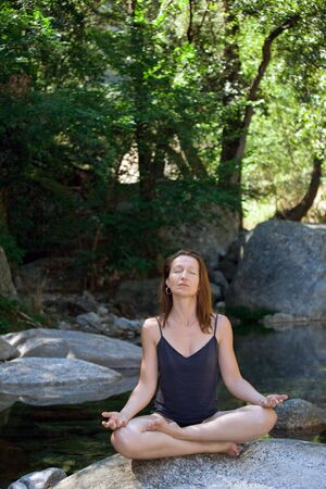 woman meditating on rock river with trees Stock Photo - 3329086