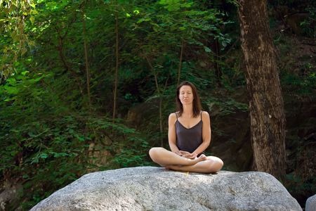 woman relaxing on big rock in forest Stock Photo - 3329085