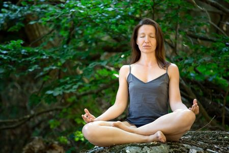 woman meditation on rock in wild forest Stock Photo - 3329082