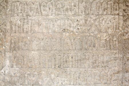 old religious carved writings on stone, romania photo