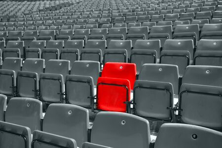 reserved seat: black and white picture of stadium seat with only one red Stock Photo