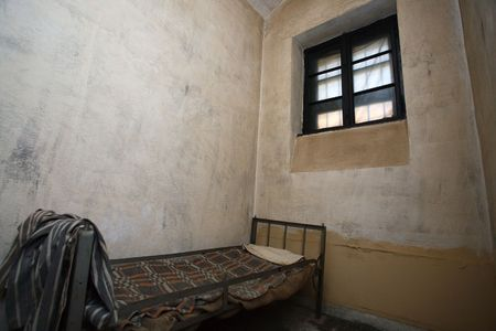 prisoner: old jail cell with clothes, bed and little window