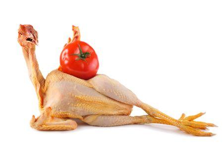 nude chicken holding big fresh tomatoe isolated on white photo