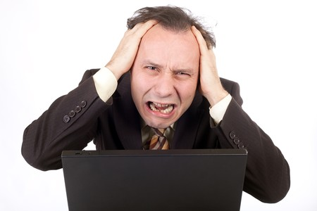 worried businessman: desperate businessman looking at computer and crying