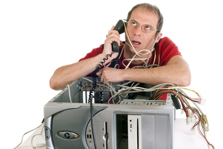 upset man lost in cables trying to repair computer and calling technician support Stock Photo