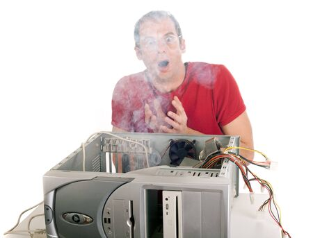 heavy smoke emerging from the computer the techinician is surprised Stock Photo
