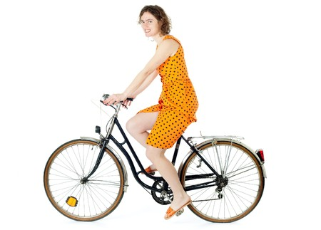 young woman in summer clothes riding bicycle on white background