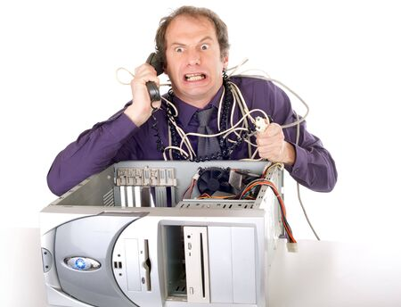 irritated businessman having computer problems phoning hotline