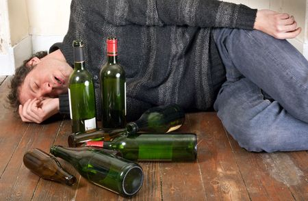 addiction alone: drunk man lying on the floor at home with many empty bottles