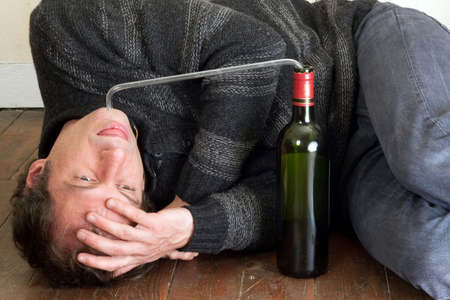 drunk man drinking wine with pipe on bottle photo