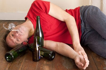 alcohol bottles: young man lying on floor smoking drug with empty alcohol bottles Stock Photo