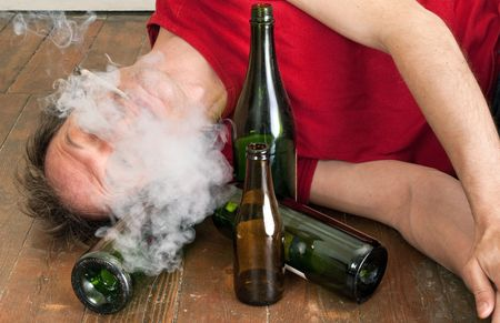 man lying on floor drinking alcohol and smoking drugs photo