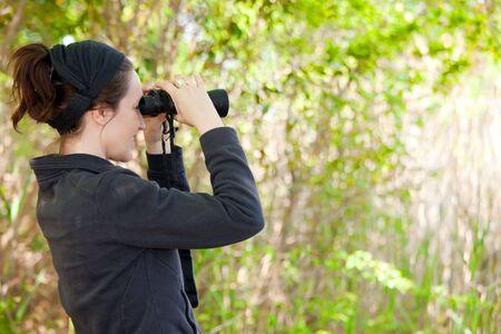 ornithology: woman watching wildlife in park with binoculars