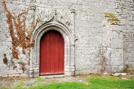 red catholic church door in brittany, france photo