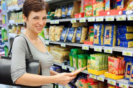 smiling woman choosing food at supermarket, all logos blurred