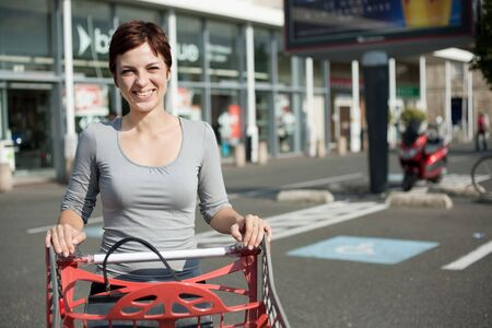 smiling woman driving shopping cart at supermarket car park photo