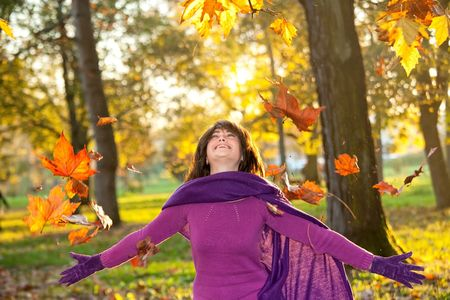 Young woman standing under falling leaves and warm sunlight smiling. photo