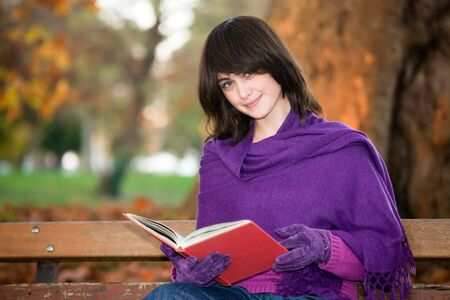 Young woman with book sitting on park bench smiling. photo