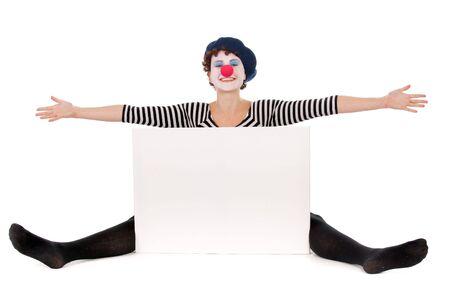 mimo: mujer de alegre payaso sentada en el suelo y presenta cartelera blanco Foto de archivo