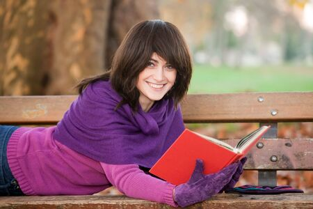 Young woman with book lying on park bench smiling. photo