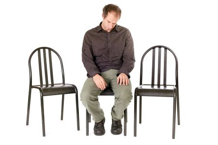 preoccupation: very sad man seated on chair alone Stock Photo