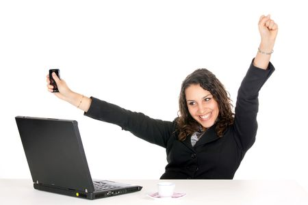 excited young business woman at office with laptop and holding cellphone photo