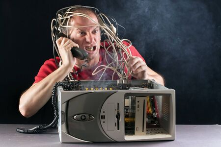 angry man having problem with his computer calling support on phone photo
