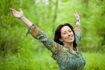 feliz mujer sonriendo y levantar los brazos en bosques verdes  Foto de archivo