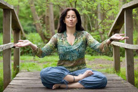 woden: woman in lotus position on woden bridge in park