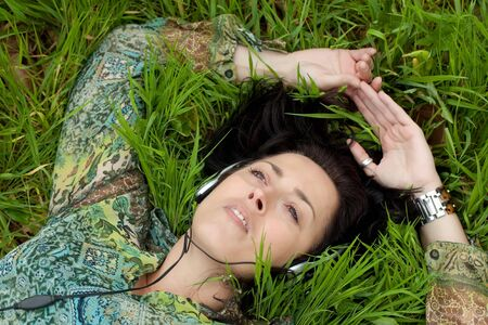 listening back: woman lying on back listening music on grass Stock Photo
