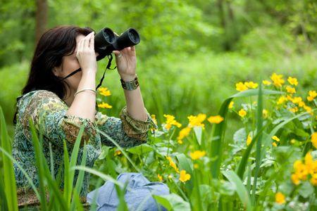 mujer en el hermoso parque observando la vida silvestre con binoculares Foto de archivo