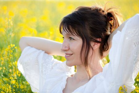 pretty woman profile portrait in rape field, selective focus photo