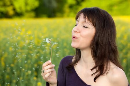 woman blowing dandelion seeds at springtime, focus on face photo