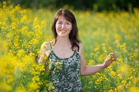 adult rape: happy woman walking in rape field at spring