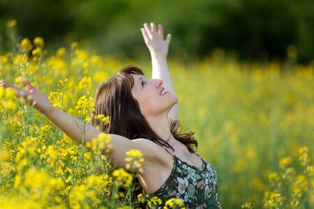 adult rape: woman in a rape field breathing and enjoying the sunlight