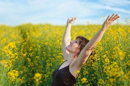 adult rape: woman enjoying spring sunlight in vivid rape field flowers Stock Photo