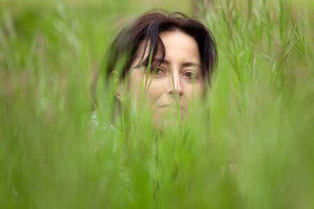 enfoque selectivo en cara de mujer oculta en la hierba