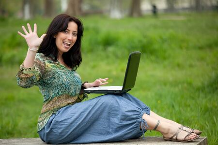 happy woman sitting on park bench using laptop photo