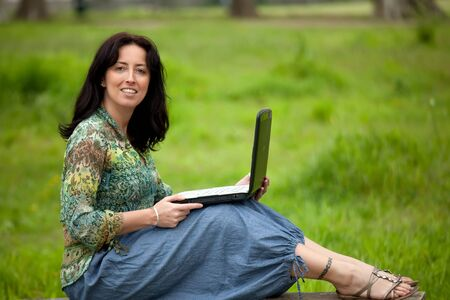 woman sitting on bench using laptop in park photo