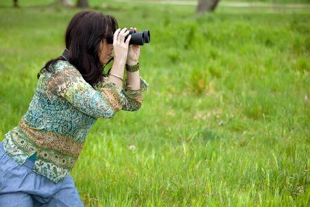 woman in meadow observing wildlife with binoculars